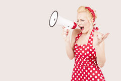 Portrait of woman holding megaphone, dressed in pin-up style red dress Stock Image