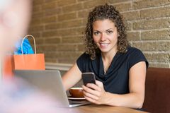 Portrait Of Woman Holding Mobilephone In Cafe. Portrait of beautiful woman with laptop on table holding mobilephone while sitting in cafe Royalty Free Stock Photos