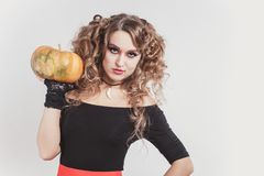 Portrait of woman holding in one hand big orange pumpkin isolated on gray background. Wearing black blouse and red skirt. Halloween celebration stock image