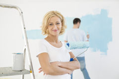 Portrait of woman holding paint roller with man painting wall in background. Portrait of women holding paint roller with men painting wall in background stock images