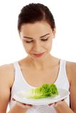 Portrait of a woman holding plate with lettuce Stock Photography