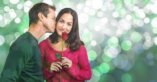 Portrait of woman holding rose while man kissing her over bokeh background stock photography