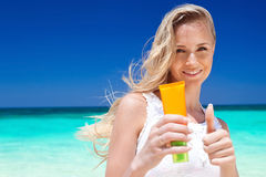Portrait of woman holding sunscreen cream Stock Photo