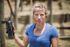 Portrait of woman holding water bottle during obstacle course. In boot camp stock images