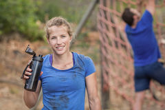 Portrait of woman holding water bottle during obstacle course. Portrait of women holding water bottle during obstacle course in boot camp royalty free stock photography