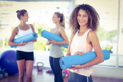 Portrait of woman holding yoga mat and smiling Royalty Free Stock Images