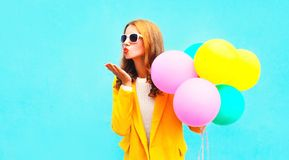 Portrait woman holds balloons sends an air kiss in yellow coat Stock Photo