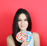 Portrait of woman holidng lollipops against red background Royalty Free Stock Photography