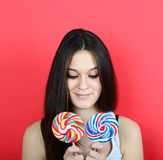Portrait of woman holidng lollipops against red background Stock Photography