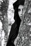 Portrait of woman with hood hiding in forest Royalty Free Stock Image