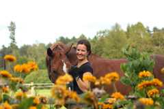 Portrait of woman with horse in flowers Royalty Free Stock Image