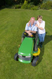 Portrait of woman hugging man on riding lawn mower Stock Photo