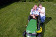 Portrait of woman hugging man on riding lawn mower Stock Images