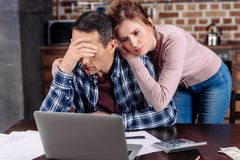 portrait of woman hugging upset husband that sitting at table with laptop at home financial royalty free stock photography