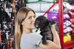 Portrait Of Woman Kissing French Bulldog At Store. Portrait of loving mid adult woman kissing French Bulldog at pet store Royalty Free Stock Photography