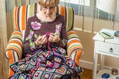 Portrait of woman knitting a vintage wool quilt Stock Images
