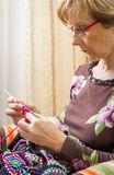 Portrait of woman knitting a vintage wool quilt Royalty Free Stock Photo