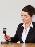 Portrait of a woman knocking a gavel stock photos