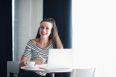 Portrait of woman laughing and looking away with a laptop in a cafe. Lady is sitting at the table near window with a cup Stock Photography