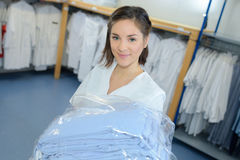 Portrait woman with laundered uniforms Royalty Free Stock Photography