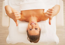 Portrait of woman laying on massage table and showing thumbs up Stock Photos