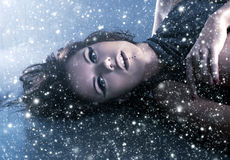 Portrait of a woman laying on a snowy background Stock Photos