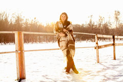 Portrait of woman leaning at fence on ranch at winter day Stock Images