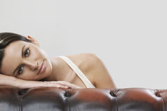 Portrait of woman leaning on sofa against gray background Royalty Free Stock Photography