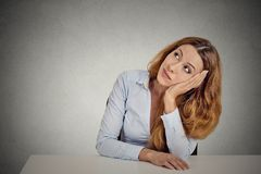 Portrait woman leaning on a white desk, thinking Royalty Free Stock Photo