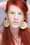 Portrait of woman with lemon slices in ears Stock Image