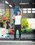 Portrait Of Woman Lifting Barbell Plate in Box. Full length portrait of young woman lifting barbell plate in box Stock Photos