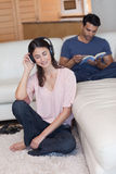 Portrait of a woman listening to music while her fiance is reading Royalty Free Stock Photography