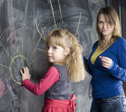 Portrait of woman and little cute girl painting on blackboard Royalty Free Stock Photos