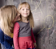 Portrait of woman and little cute girl painting on blackboard Stock Photography