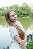 Portrait of a woman with long hair near the lake. Eyes closed Stock Photos