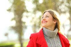 Portrait of a woman looking above outdoors in winter. Portrait of a funny woman wearing red jacket looking above outdoors in winter Royalty Free Stock Image