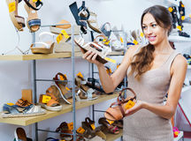 Portrait of woman looking confused with two pair of shoes Royalty Free Stock Image