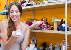 Portrait of  woman looking after pair of shoes for kid Royalty Free Stock Photos