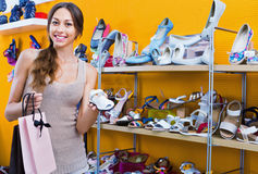 Portrait of  woman looking after pair of shoes for kid Royalty Free Stock Photo