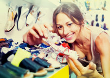 Portrait of  woman looking after pair of shoes for kid Royalty Free Stock Photography