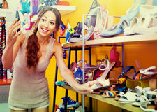 Portrait of  woman looking after pair of shoes for kid Royalty Free Stock Images