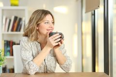 Woman looking through a window drinking coffee. Portrait of a woman looking through a window drinking coffee sitting in a table at home Royalty Free Stock Image