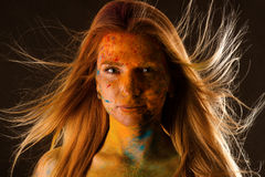Portrait woman in luxurious colors Holi with flying hair Stock Photo