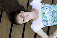 Portrait of woman lying on deck. Woman lying on deck with hair spread out royalty free stock image