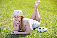 Portrait of woman lying on green lawn in park on summer day Stock Photography