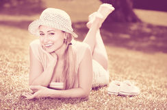Portrait of woman lying on green lawn in park on summer day Stock Photo