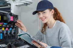 Portrait woman maintaining photocopier Royalty Free Stock Photography