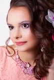 Portrait of a woman with make-up with pink decoration technique. Portrait of curly brunette with purple make-up in pink dress with soutache technique decorations Royalty Free Stock Photography