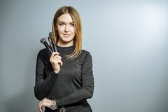 Portrait of a woman makeup artist with the makeup brush on a gray background royalty free stock photos