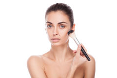 Portrait of woman with makeup brush near her face Stock Photos